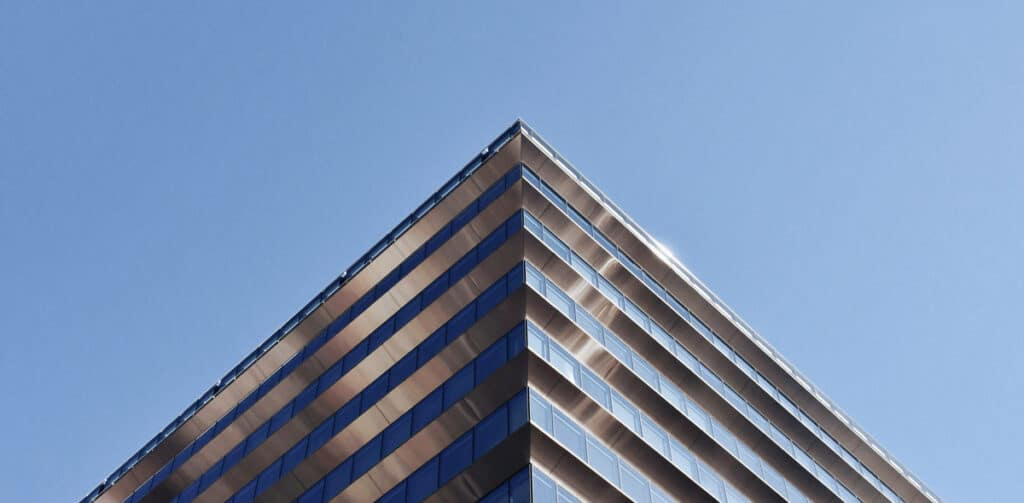 Dramatic angle looking up at a commercial modern building's edge.