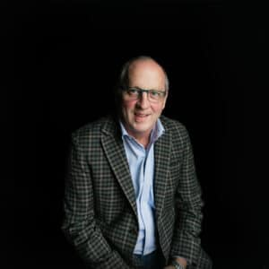 Ken Barrick, broker of record, smiling with dark background.