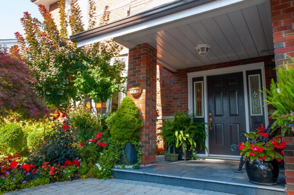 Front door area of a home with black door and red flowers.
