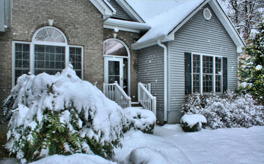 Front of urban home with snowfall and snow coverage.